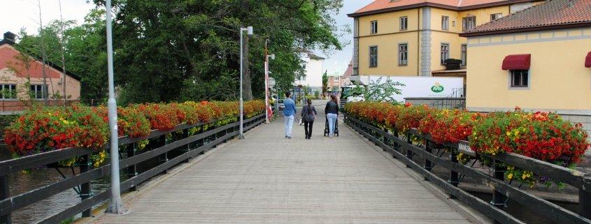 Blomsterbåtar längs räcket på en bro