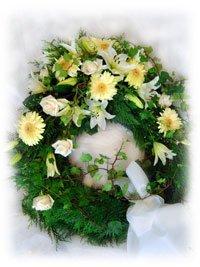 Krans i vita toner med bl.a. liljor, gerbera och rosor.