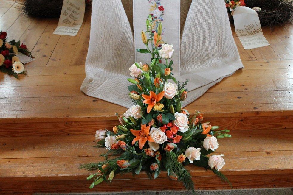 begravningsdekoration, orange liljor, ljusa rosor